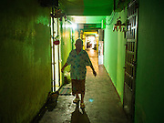 24 FEBRUARY 2015 - PHNOM PENH, CAMBODIA: A resident walks through a hallway in the White Building. The White Building, the first modern apartment building in Phnom Penh, originally had 468 apartments, and was opened the early 1960s. The project was overseen by Vann Molyvann, the first Cambodian architect educated in France. The building was abandoned during the Khmer Rouge occupation. After the Khmer Rouge were expelled from Phnom Penh in 1979, artists and dancers moved into the White Building. Now about 2,500 people, mostly urban and working poor, live in the building. Ownership of the building is in dispute. No single entity owns the building, some units are owned by their occupants, others units are owned by companies who lease out apartments. Many of the original apartments have been subdivided since the building opened and serve as homes to two or three families. The building has not been renovated since the early 1970s and is in disrepair. Phnom Penh officials have tried to evict the tenants and demolish the building but residents refuse to move out.   PHOTO BY JACK KURTZ