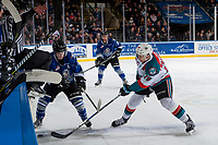 KELOWNA, CANADA - FEBRUARY 12:  Carsen Twarynski #18 of the Kelowna Rockets digs for the puck at the boards ahead of Matthew Phillips #11 of the Victoria Royals on February 12, 2018 at Prospera Place in Kelowna, British Columbia, Canada.  (Photo by Marissa Baecker/Shoot the Breeze)  *** Local Caption ***