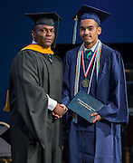 Dameion Crook presents Salutatorian Jonathan Bond with the second diploma during the first ever graduation for Mickey Leland College Preparatory Academy, May 27, 2015.