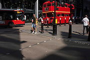 A red Routemaster bus drives along Cannon Street in the City of London, UK.