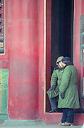 Two men in Mao suits stand in a doorway of the Forbidden City during a snow storm in Beijing, China