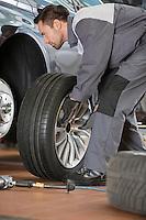 Full length of male mechanic fixing car's tire in repair shop