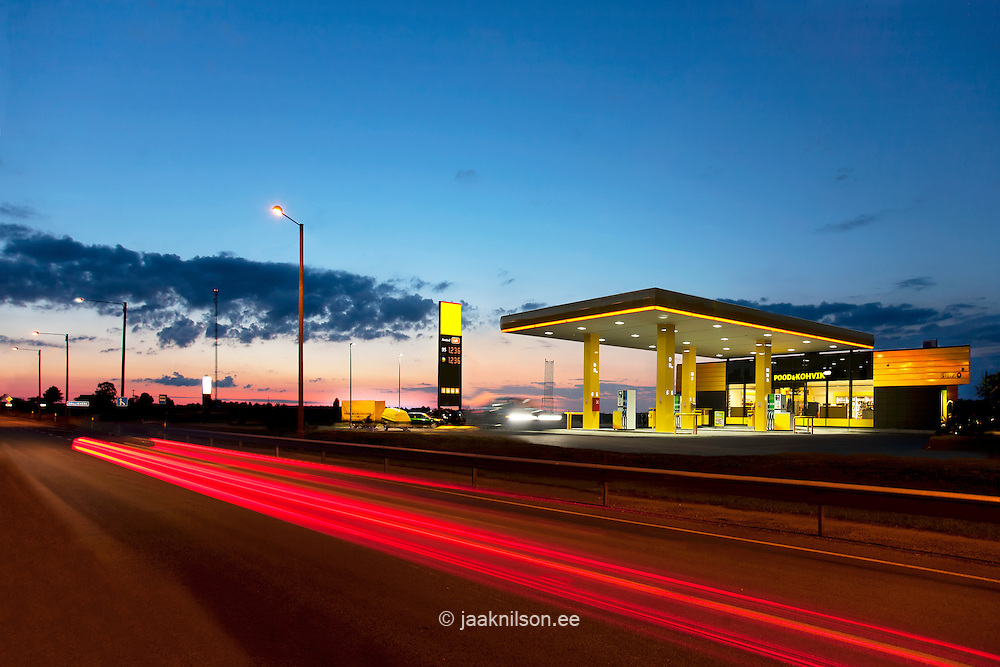 Lighted roadside gas station at night in Estonia. Highway, car tail lights. Light trail.