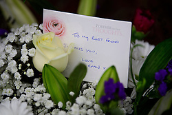 © Licensed to London News Pictures. 15/12/2016. London, UK. Flowers and a note left in the doorway of a property on The Fairway in Ruislip where the bodies of a woman and a boy were discovered. Police forced their way into the West London home yesterday morning and discovered the body of a 37 year old woman and a seven year old boy. Photo credit: Ben Cawthra/LNP