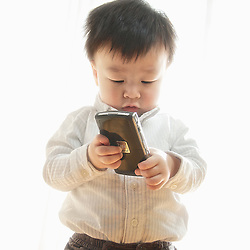 Asian male toddler plays with a blackberry mobile cell phone