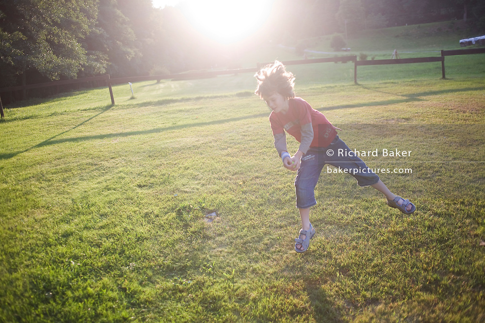 A young boy leaps to catch a tennis ball on summer grass in setting backlit sun in Germany's Black Forest.
