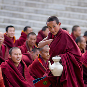 Novice monk handing out serving tea and bread at Labrang Monastery, Xiahe, China