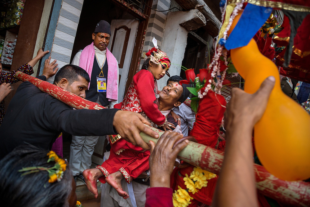 Careful not to pollute herself by touching the ground on a day when the power of the goddess has been invoked, Kumari Dangol is carried by her father to a palanquin that will bear her above the crowds during the festival of Bisket Jatra.