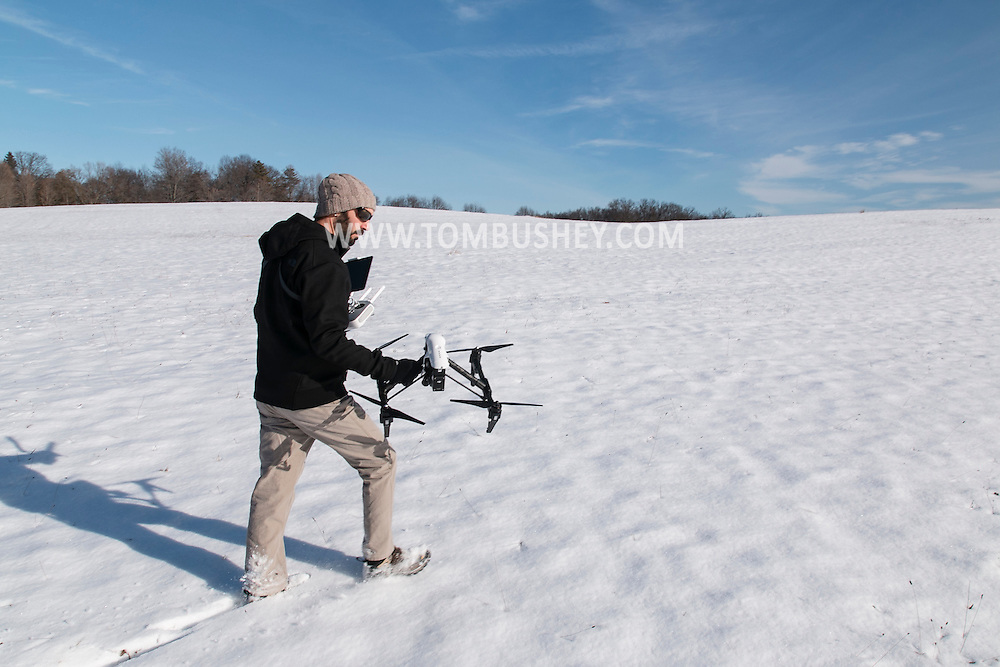 Montgomery, New York - Adam Pass walks with his DJI Inspire 1 quadcopter before flying the drone at Benedict Farm on Jan. 25, 2015.