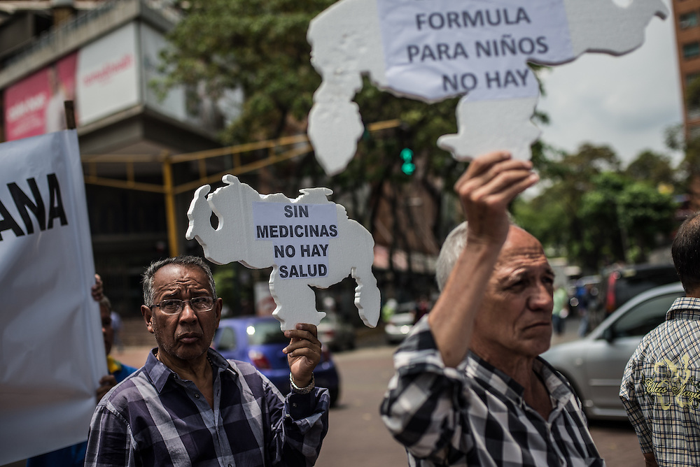 """CARACAS, VENEZUELA - APRIL 13, 2016:  Doctors, patients and their families block traffic during a protest against the hospital crisis.  These men hold signs cut in the shape of Venezuela,  that say in Spanish, """"There is no health without medicines"""" and """"There is no formula for kids"""". Despite having the largest oil reserves in the world, falling oil prices and wide-spread government corruption have pushed Venezuela into an economic crisis, with the highest inflation in the world and chronic shortages of food and medical supplies.  PHOTO: Meridith Kohut for The New York Times"""