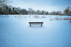 Park bench in the snow covered Arboretum, Evington Village, Leicester, England, UK.
