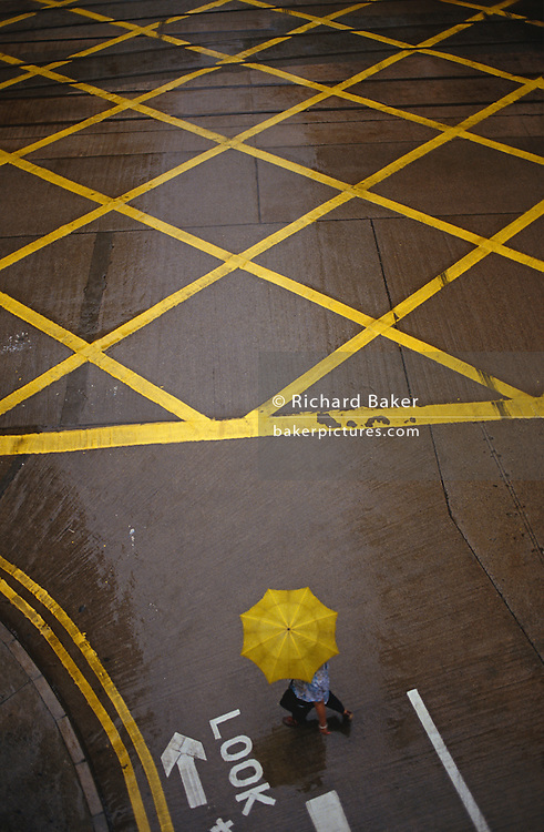 """In light monsoonal rain, a lone pedestrian is seen from a high viewpoint, crossing a zebra crossing with a yellow grid box junction to his right in Central Hong Kong on the last day of British rule. The junction is empty and without any traffic but the word 'Look' is stencilled in white letters for the benefit of unwary pedestrians. An umbrella used by the unrecognisable person is a colour match with the painted striped road markings, identical to the British highway traffic code. The transfer of sovereignty of Hong Kong from the United Kingdom to the Peoples Republic of China (PRC), often referred to as """"The Handover"""" occurred at midnight on June 30, 1997, signifying the end of British rule, and the transfer of legal and financial authority back to China. Hong Kong was once known as 'fragrant harbour' (or Heung Keung) because of the smell of transported sandal wood."""