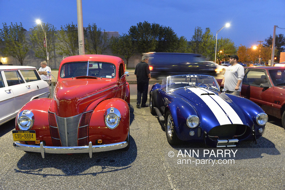 Bellmore, New York, USA. 12th June 2015. A vintage red Ford Deluxe roadster and a classic blue with white striped 437 Cobra racing car are on display at the Friday Night Car Show held at the Bellmore Long Island Railroad Station Parking Lot. Hundreds of classic, antique, and custom cars were on view at the free weekly show, sponsored by the Chamber of Commerce of the Bellmores.