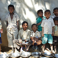 Students at the Jalhe Bogiya village school wait to be served as part of the midday meals program. ..Lack of irrigation and food security lie at the root of the Maha Dalit community's problems in the village of Jalhe Bogiya. In the exploitative and divisive caste system, Maha Dalits are considered the lowest of the low. Ostracized by wider society (including the administration) illiteracy runs as high as 95 percent. Jalhe Bogiya now has an - as yet incomplete - access-road built as part of the NREGA (National Rural Employment Guarantee Scheme). Intervention by NGOs in summer 2010 successfully lobbied the local administration to implement the provision of school midday meals which, by law is the right of every child. It is alleged that the Anganwadi (pre-school) centre administrator, syphons off food meant for young children. Jalhe Bogiya has several hand pumps supplying water but these do not work between the months of May to October. And though the village was connected to the electricity grid six months ago, power-supply is not reliable. Without land-ownership and only irregular agricultural work from which to earn an income, the Maha Dalits of Jalhe Bogiya frequently migrate in search of labour at stone breaking quarries, brick-kilns or undertake menial household work in the homes of the urban middle class in far-away cities. ..Photo: Tom Pietrasik.Mohanpur Block, Gaya District, Bihar. India.February 23rd 2011