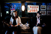 GOP presidential candidate Gov. Mitt Romney pres secretary Andrea Saul, left, and production director John Legittino, right, work on the campaign bus after  a campaign rally at Carter Machinery Company in Salem, Virginia, June 26, 2012.