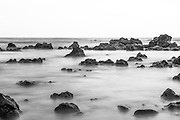 The tide flows in and out of the volcanic rocks in Hana Bay on the island of Maui, Hawaii.