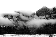Clearing storm and snow covered trees in Yosemite Valley at Cooks meadow looking toward Yosemite falls