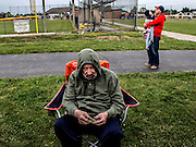 Tom Engeman sits apart from the crowd at his granddaughter, Reeses's tee-ball game. Tom has no idea he is at a tee-ball game or that it is his granddaughter playing. Tom doesn't recognize his life anymore. Eight years ago he was diagnosed with Alzheimer's. In the background Tom's other grandchild, David, is being held by his healthy grandfather, also David.