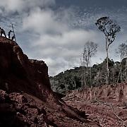 Brasile, Amazzonia, garimpo de Juma. Le miniere a cielo aperto del garimpo de Juma, dove la vita dei minatori scorre tra pericolo per un lavoro al limite e deforestazione incontrollata. Aspettando di trovare l'oro che cambi la loro vita. In questa foto tre minatori lavoro pericolosamente sul ciglio di una montagna. Brazil, Amazonia, garimpo de Juma. The open pit mines of garimpo de Juma, where the miners work flows between danger and uncontrolled deforestation. Waiting to find the gold that changes their lives. In this picture three miners working dangerously on the edge of a mountain.