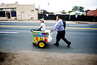 A father pushes his son and a ice cream cart down the 3500-block of  Brighton Blvd. in Denver, Colo. on Saturday, Sept. 17, 2011.