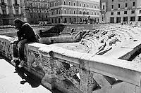 Lecce - Salento - Un extracomunitario si riposa sul muretto dell'Anfiteatro Romano.
