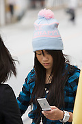 Kokusai-do?ri amusement and shopping street. Young girl with wool cap and mobile phone.