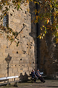 Locals sit in afternoon sunshine beneath the tall outer wall of Hexham's Moot Hall, on 29th September 2017, in Hexham, Northumberland, England. Originally, this gatehouse guarded the hall of the archbishops of York who were the Lords of the manor of Hexham for nearly 500 years until 1545. In later centuries the gatehouse became the setting for the Quarter Sessions of county magistrates and for the meetings of the town's Borough Courts, Since then it has been called the Moot Hall.