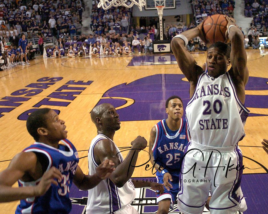 Kansas State's Cartier Martin (20) pulls down a rebound over Kansas center C. J. Giles (33) and guard Brandon Rush (25), during the first half at Bramlage Coliseum in Manhattan, Kansas, March 4, 2006.  The Jayhawks won 66-52.