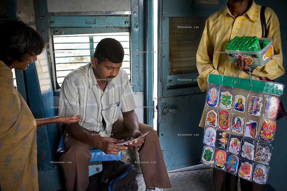 A passenger sifts through stickers of deities and cartoons while a beggar begs for money on the Himsagar Express 6318 as it passes through the south Indian state of Tamil Nadu on 9th July 2009.. .6318 / Himsagar Express, India's longest single train journey, spanning 3720 kms, going from the mountains (Hima) to the seas (Sagar), from Jammu and Kashmir state of the Indian Himalayas to Kanyakumari, which is the southern most tip of India...Photo by Suzanne Lee / for The National