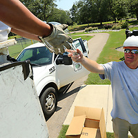 Will Vaughn, an employee with Tupelo, Water & Light, hands fellow worker Daniel Johnson a new bulb as they check the lighting and replace old bulbs as needed at the Tennis Courts at Rob Leake Park Monday afternoon in Tupelo to ready the courts for an upcoming Tennis tournament this weekend.