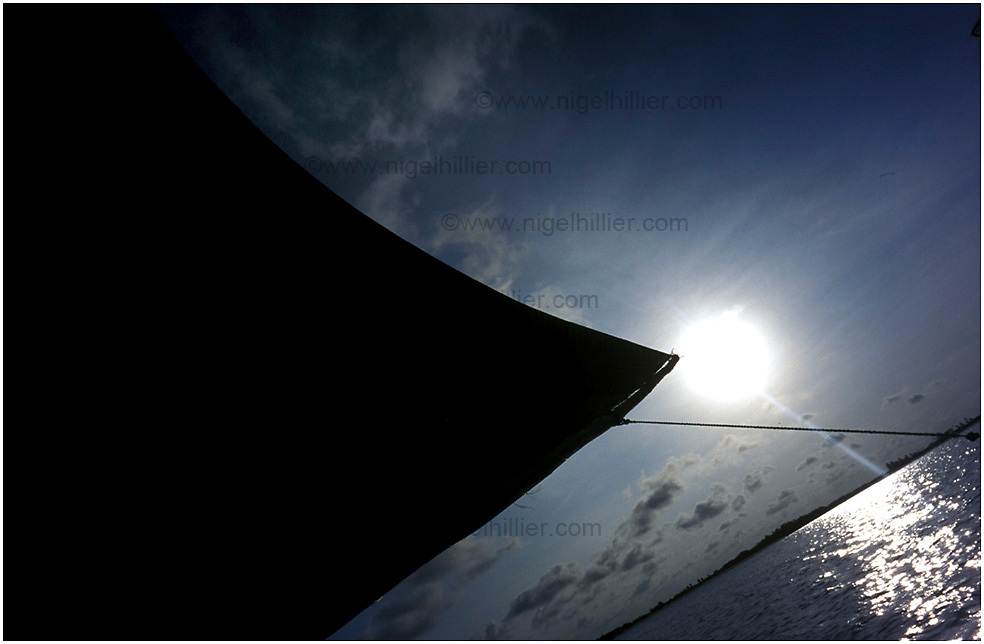 copyright: Nigel Hillier.Brazil, Maranhao, Parque National Dos Lencois, Maranhenses, silhouette of fishing boat sail