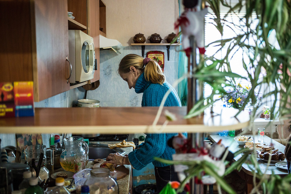 DNIPROPETROVSK, UKRAINE - OCTOBER 12: Svitlana Kostromina in the kitchen at the home where she, her daughter, and her granddaughter are living with a family in their church's congregation after fleeing fighting in Luhansk in Ukraine's East on October 12, 2014 in Dnipropetrovsk, Ukraine. The United Nations has registered more than 360,000 people who have been forced to leave their homes due to fighting in the East, though the true number is believed to be much higher. (Photo by Brendan Hoffman/Getty Images) *** Local Caption *** Svitlana Kostromina
