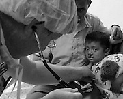 Nurse Anesthetist Mike Serafine evaluates a child for repair of his cleft lip.