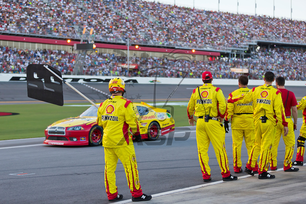 DAYTONA BEACH, FL - JUL 07, 2012:  The Shell Pennzoil crew wave at their driver, Sam Hornish, Jr. before the start of the Coke Zero 400 at the Daytona International Speedway in Daytona Beach, FL.  Sam Hornish was a last minute replacement for the suspended A.J. Almendinger (22) due to failing a drug test administered the week before in Sparta, KY.