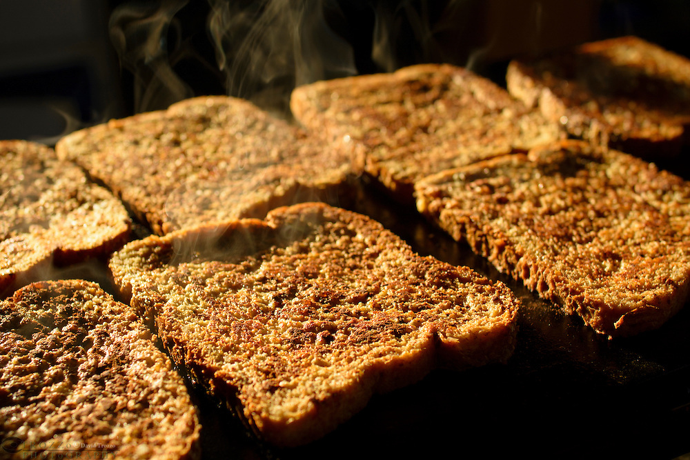 Steamy hot French toast with cinnamon being fried on a griddle pan.