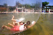 Israel, Holon, Children in a summer camp are playing inside giant plastic balloons that are rolling over the water at Peres park