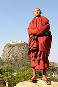 Monk standing before the famous monastery of Mount Popa, Myanma