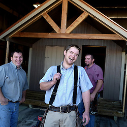 David Petershiem, center, laughs along with with fellow workers and Mennonites Martin Kauffman, left, and Ed Coblentz during work at the 5 Star-Buildings in Cuba, Missouri on Wednesday, Sept. 28, 2016. The business builds and delivers small and large portable buildings. (Photo by Keith Birmingham Photography)
