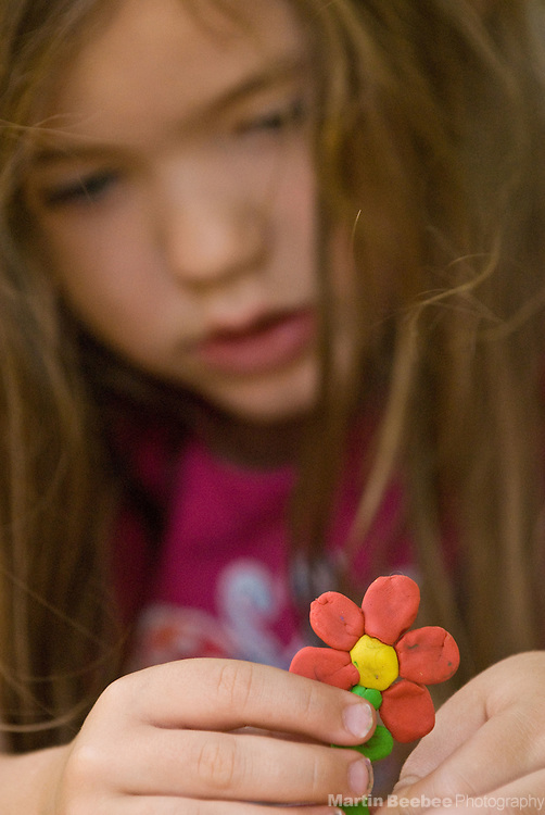 A four-year-old girl works on a clay flower