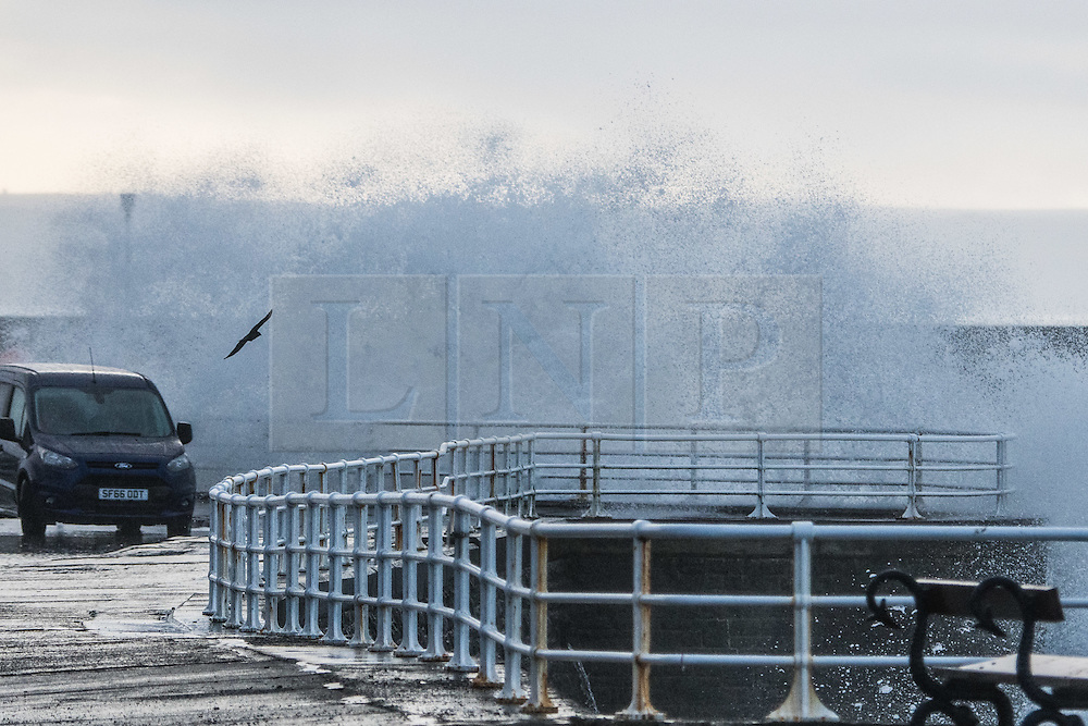 © Licensed to London News Pictures. 21/12/2016. Aberystwyth, Wales, UK. On the shortest day of the year, the Winter Solstice, a change in the weather brings showers of rain and  gusty winds combined with the  high tide to drive huge waves to batter the seafront and harbor wall at Aberystwyth on the Cardigan Bay coast of the Irish Sea in West Wales UK. Photo credit: Keith Morris/LNP