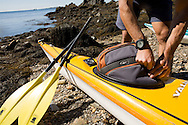 A camper loads his backpack into the kayak on Jewel Island, Maine