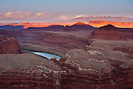 The rugged canyons of Canyonlands National Park turn orange and purple at dusk as they extend in all directions as seen from The White Rim Trail near Moab, Utah. The canyons have been cut over eons by water, wind and the elements creating a rugged landscape that are a playground for adventurers and hideaways for outlaws.