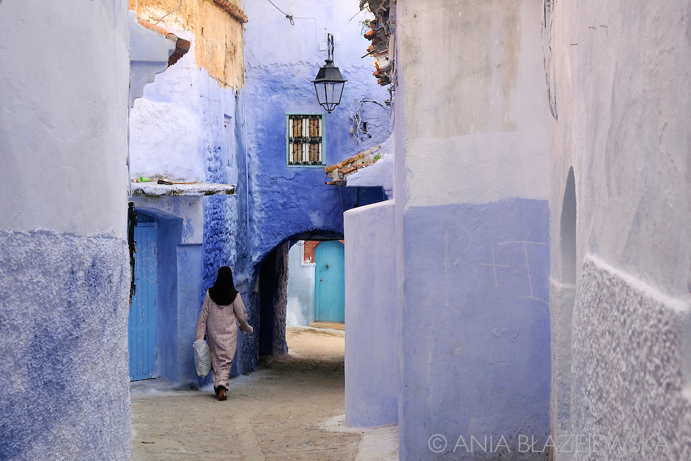 Morocco, Chefchaouen. Woman walking among the walls of the blue medina.