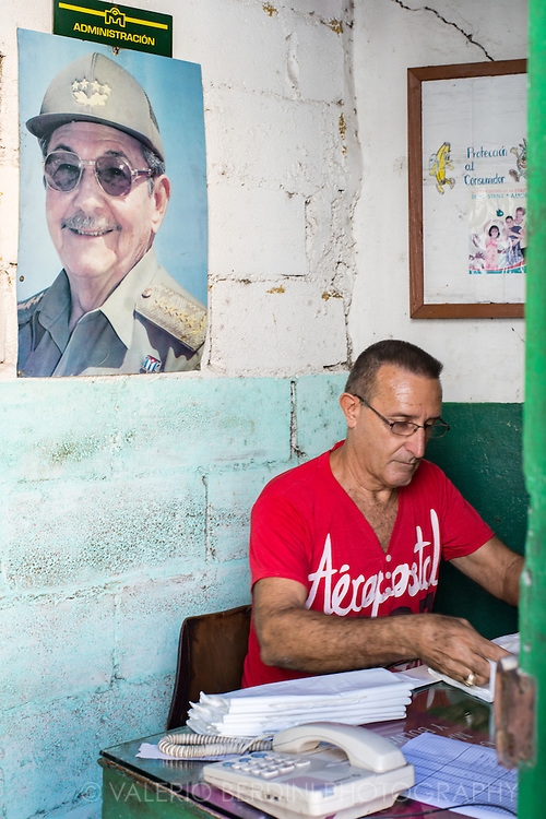 A man sits in a administrative office of a street shop in Havana. A poster of smiling Cuban President Raul Castro is on the wall. Cuba, 2015.