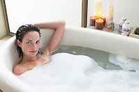 Young woman relaxing in bubble bath elevated view