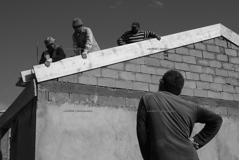 construction workers erecting a refugee village in the outskirts of georgian town Gori. About 160 houses are under construction at the scene to give shelter to the georgian refugees after the south ossetian war. Several villages this kind are under contruction in Georgia.