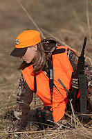 FEMALE HUNTER IN BLAZE ORANGE CARRYING A BLACK, AR-STYLE GUN