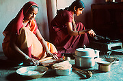 INDIA, VILLAGE LIFE a rural family making traditional chapatties (wheat cakes) in their kitchen in Central India