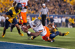 Oct 10, 2015; Morgantown, WV, USA; Oklahoma State Cowboys running back Rennie Childs dives for a touchdown during the second quarter against the West Virginia Mountaineers at Milan Puskar Stadium. Mandatory Credit: Ben Queen-USA TODAY Sports