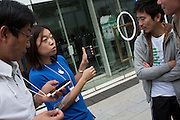 Apple employees demonstrate the new iphone to  those in line at the Apple store awaiting the official release of the iphone4S in Ginza, Tokyo, Japan. Friday October 14th 2011. The latest version of the popular iphone was released worldwide on October 14th. Japans flagship Apple store in Ginza was opened at 8am for the 800 people that had been waiting to be the first to purchase the new telephone.